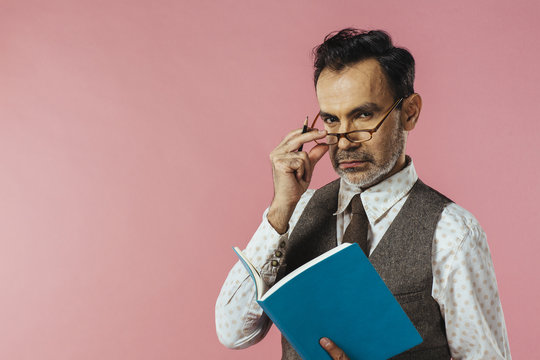 Portrait of  a mature man in vest holding notebook, glasses and notebook, isolated on pink