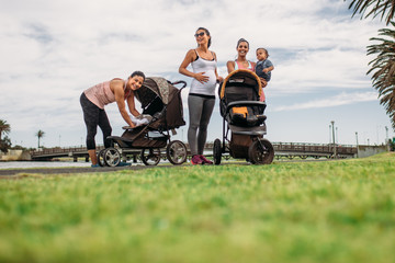 Mothers on a morning walk with their kids in baby prams