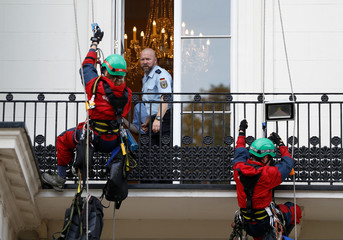 A German police officer watches as Greenpeace activists prepare to climb on to a balcony after they deployed a banner against coal outside Germany's embassy in London