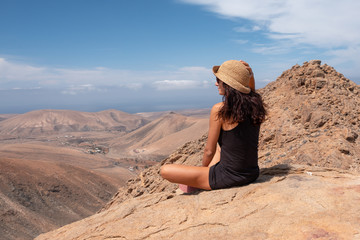 relaxed girl looking at a landscape from the top of a mountain