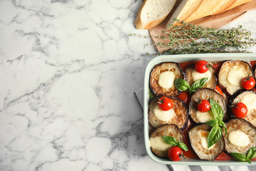 Flat lay composition with baked eggplant, tomatoes and basil in dishware on marble table. Space for text