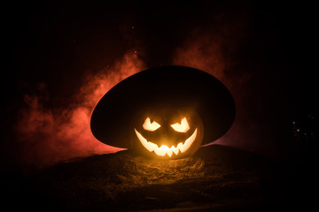 Halloween concept. Jack-o-lantern smile and scary eyes for party night. Close up view of scary pumpkin with witch hat on at dark foggy background. Selective focus.