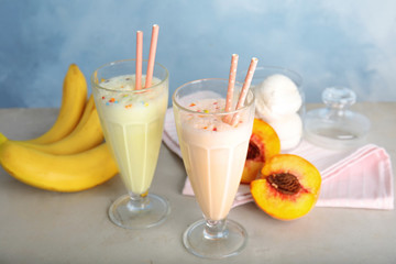 Delicious milk shakes and ingredients on table against color background
