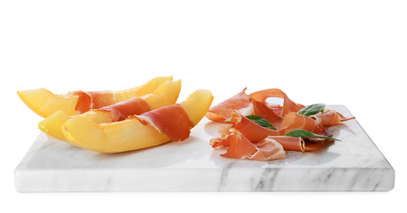 Board with melon slices and prosciutto on white background
