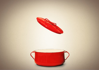 Big red pot for soup on the brown background