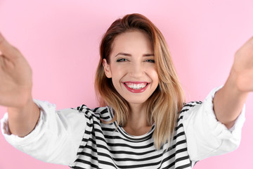 Beautiful laughing woman taking selfie on color background