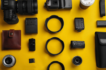 Flat lay composition with photographer's equipment and accessories on color background