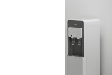 Modern water cooler near white wall indoors. Space for text