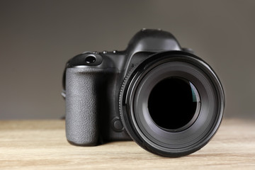 Digital camera of professional photographer on table