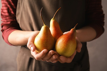 Woman holding ripe pears on grey background, closeup
