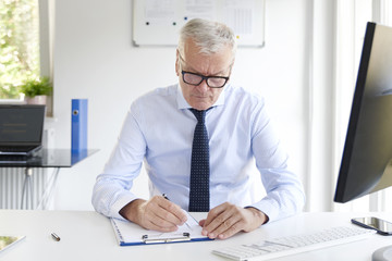 Thinking senior businessman writing something
