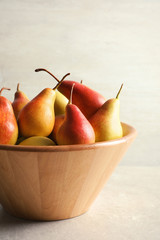 Bowl with ripe pears on table against light background