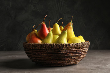 Wicker bowl with ripe pears on table against dark background