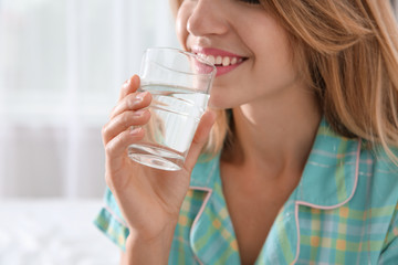 Young woman drinking water from glass indoors, closeup