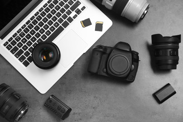 Professional photographer equipment and laptop on gray background, top view