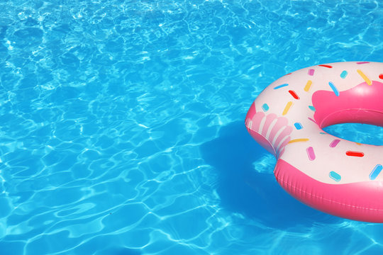 Inflatable ring floating in swimming pool on sunny day. Space for text