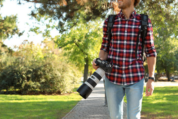 Young male photographer with professional camera in park. Space for text
