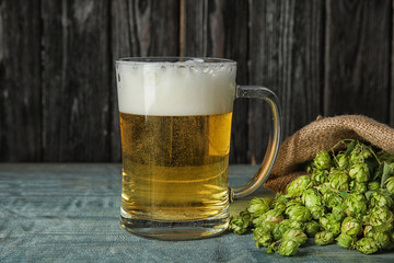 Composition with tasty beer and fresh green hops on wooden table