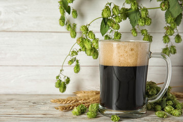 Composition with tasty beer, wheat spikes and fresh green hops on wooden table. Space for text