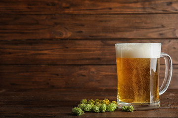 Composition with tasty beer and fresh green hops on wooden background. Space for text