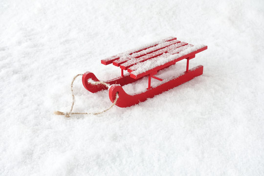 Red Wooden Sledge in Snow covered with Snowflakes