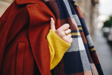 detail of woman wearing winter clothes and a gold ring. street style.