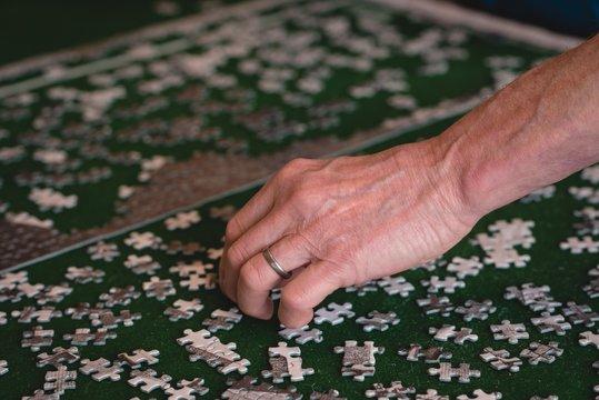 Senior man playing puzzle game at home