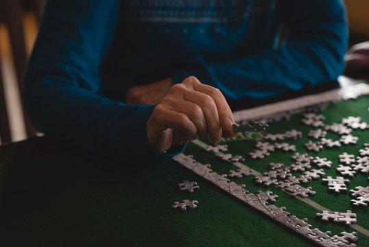 Senior woman playing jigsaw puzzle at home