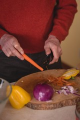 Senior man cutting carrot with knife in kitchen