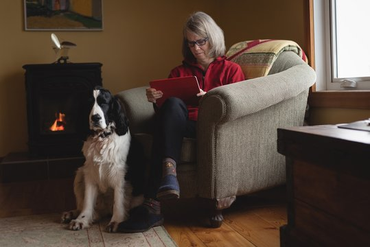 Woman using digital tablet with dog sitting beside her