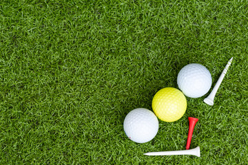 Different golf balls and tee on the green grass background.Golf set concept.Sport equipment.