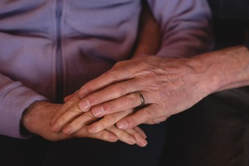 Senior couple holding hands at home