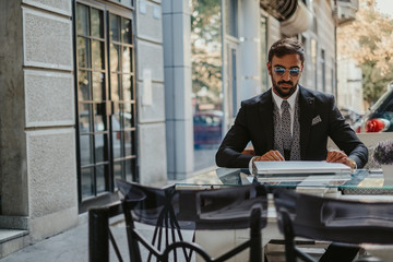 Businessman in a suit opening laptop in a cafe