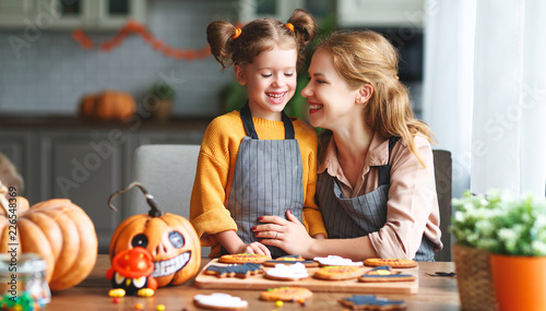 happy Halloween! family mother and daughter getting ready for   holiday and baking cookies