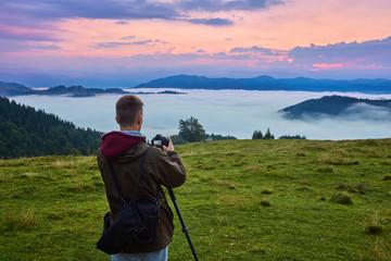 Professional photographer takes photos with camera on tripod on rocky peak.