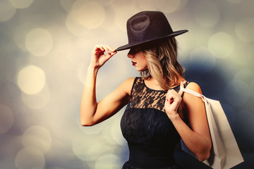 Portrait of a young style girl in black dress and hat with shopping bags on gray background with bokeh
