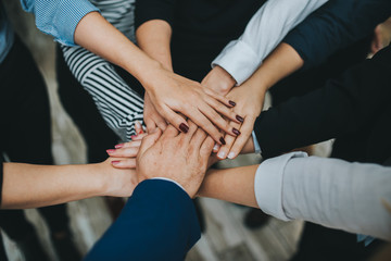 Group of business people team joining hands together in office.