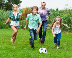 Happy family of four people playing football