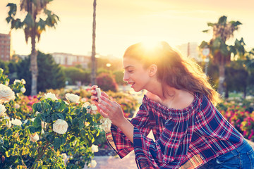 Girl taking smartphone photo to rose flower
