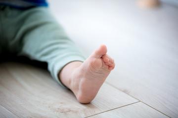 little boy foot in pants on floor. Coseup view