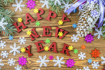 New Year's celebratory background of light brown color with spruce branches, snowflakes, congratulations.