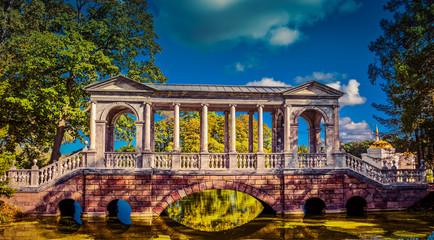 Landmark of city Pushkin – empty colorful marble (palladium) bridge on pond in sunny summer day. Catherine garden, Tsarskoe selo, Saint-petersburg, Russia, Europe