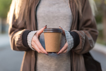 Women holding brown paper cup in two hands