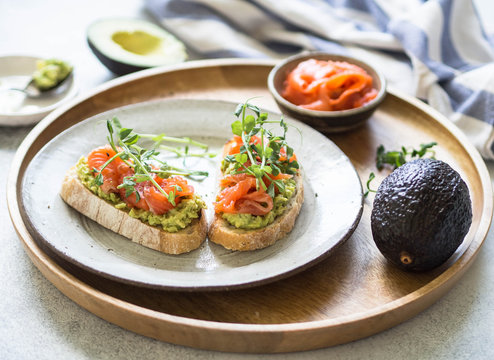 Toasts with avocado and salted salmon with fresh pea sprouts on a plate on a wooden tray