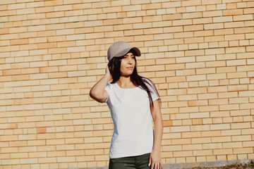 Young sexy swag girl. Outdoor lifestyle portrait of female in brown cap. Summer photo toned style Instagram filters