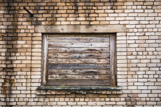 Boarded window on brick building