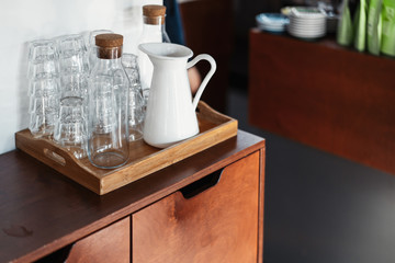 Transparent glasses and white metal jar on wooden cupboard in cafe.