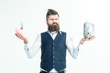 Business, finances, investment, money saving concept. Worried bearded man holds piggy bank&jar of money. Key to business&finance measurement concept. Money. Benefit. Thrifty man taking care of future.