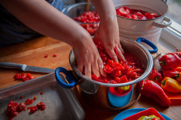 woman cook in an apron prepares tomatoes in a saucepan, rubs through a sieve and prepares tomato juice. Female hands closeup.