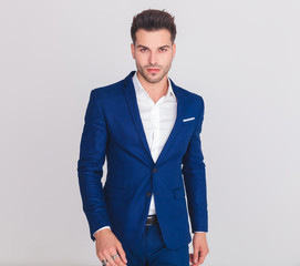 portrait of elegant handsome man in blue suit walking